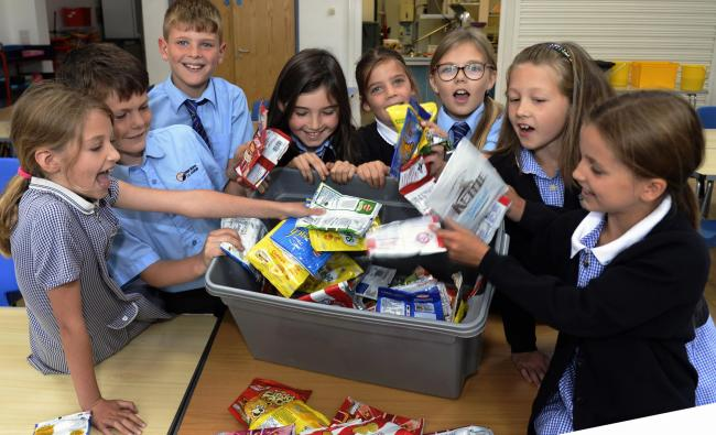 EXCITED: Pupils pictured with their crisp packets collected from the school grounds    Photo: Jon Granger