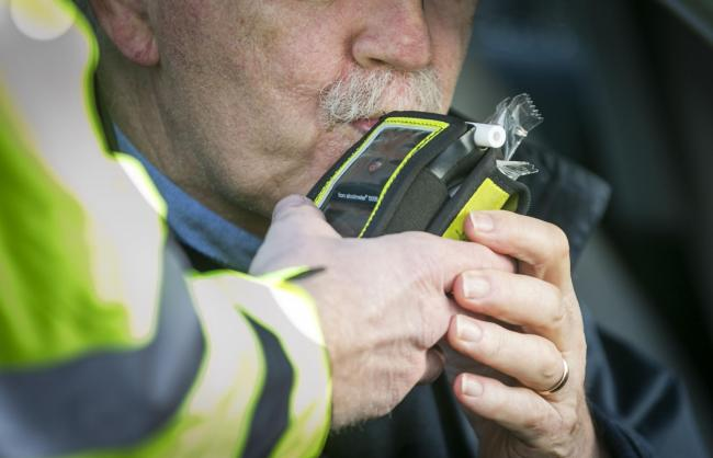 A driver blows into a PSNI Road Policing officers' breathalyser during a random drink driving checkpoint in Belfast..