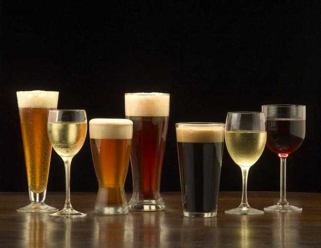 """An assortment of glasses of wine and beer including a classic pilsner flute, a sparkling wine glass, an American half pint glass, a weizen or wheat beer glass, an American pint glass, a white wine glass, and a red wine glass.""."