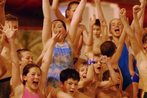 CHEERS Arms are raised at the climax of a close race at the swimming gala held in March 2002.
