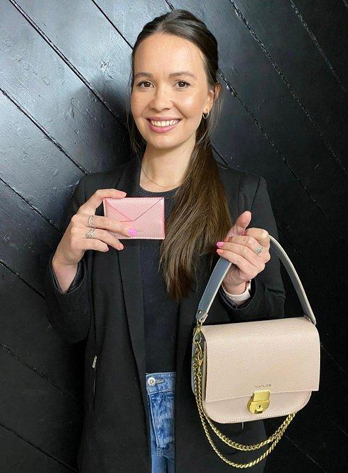 Aimee Duclos, owner and founder of Duclos, holding a Duclos cardholder and Fika handle strap bag
