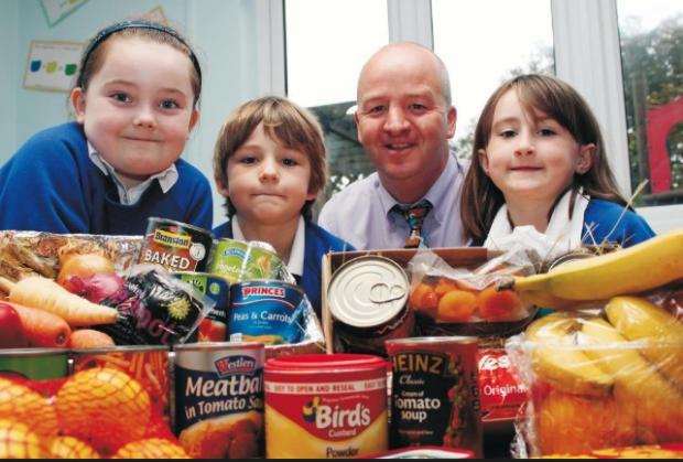 The Mail: SMILES: Charlotte North, Lucas Messenger-Jones and Charli Smith with headteacher Mr Lewis at Ireleth St Peter's in 2010
