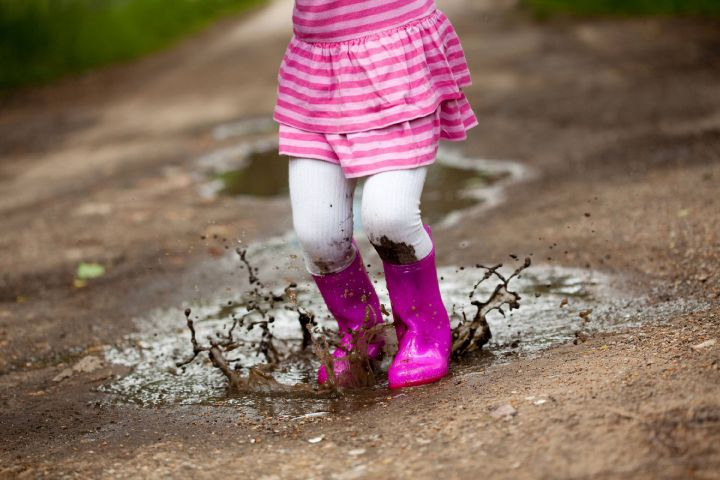 A young girl jumping into a muddy puddle