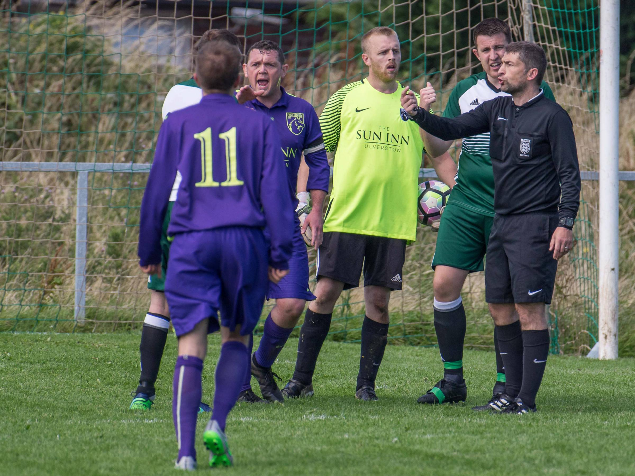 Referee Colin Atkinson tries to calm things down