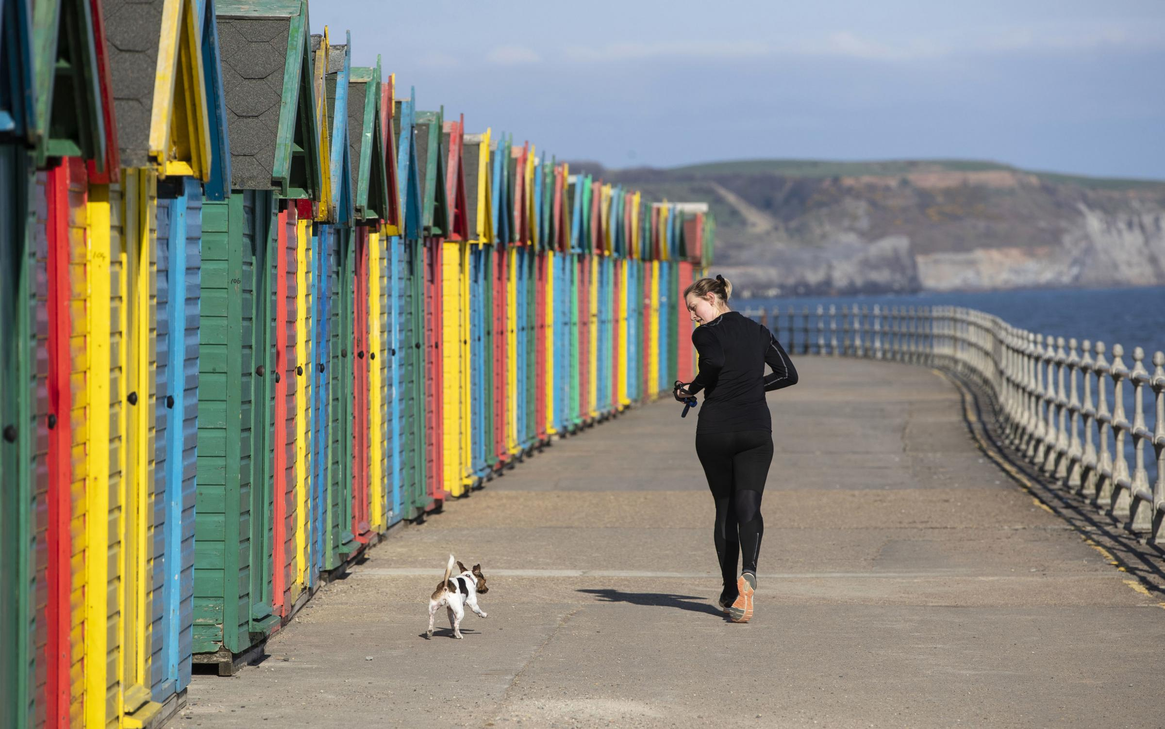 A woman jogging with her dog near colourful beach huts on Whitby beach in Yorkshire. PRESS ASSOCIATION Photo. Picture date: Friday April 12, 2019. See PA story WEATHER Spring. Photo credit should read: Danny Lawson/PA Wire.