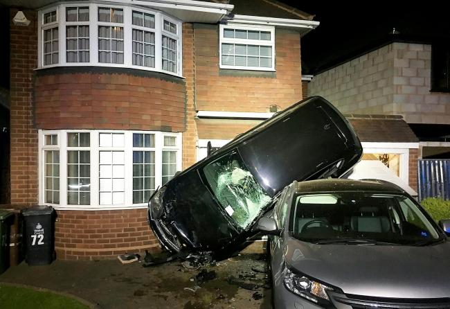 A suspected drink driver cheated death when he flipped a car over another parked vehicle and missed a house by a matter of inches.  See SWNS story SWMDflip.  Dramatic pictures of the scene show the black car almost resting upright after the smash in the e