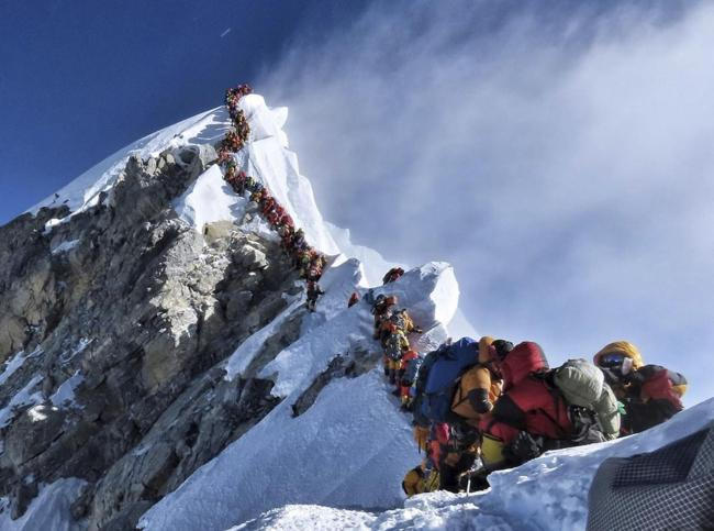 In this photo made on May 22, 2019, a long queue of mountain climbers line a path on Mount Everest. About half a dozen climbers died on Everest last week most while descending from the congested summit during only a few windows of good weather each May.