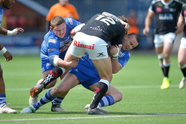 Jono Smith tries to get to grips with Widnes' Chris Dean