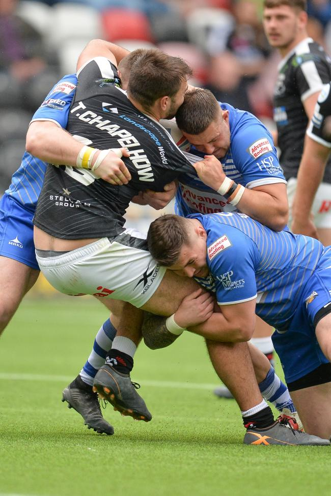 Widnes' Ted Chapelhow is halted at the Halton Stadium